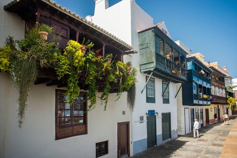 Balcones repletos de plantas en una casas de color blanco y de diferentes colores de balcones.