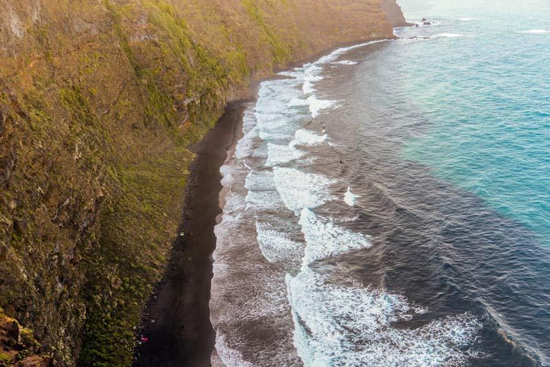 Vista aerea de la playa de arena negra desde un lateral donde podemos observar su vertical acantilado en la parte de atrás.