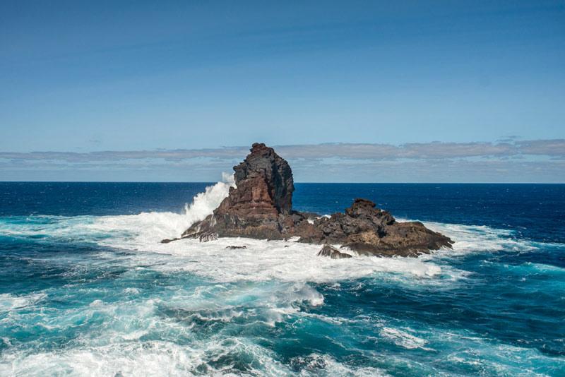 Roque en medio del mar abatido por las olas. El atlántico azul y las olas de color blanco al embestir contra el roque.