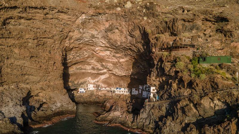 Vista de un pueblo que se encuentra de una gran bóveda oradada en un acantilado. Perder el rumbo