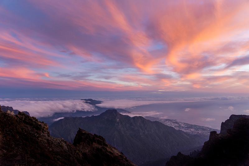 Vista de una puesta de sol de colores Violeta anaranjados desde lo alto del roque de los muchachos. Al fondo de ve Tazacorte.
