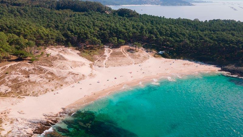 Playa de Melide con aguas cristalinas y turquesas y rodeada de verdes pinos. 20 lugares que ver en Galicia imprescindibles. Perder el Rumbo