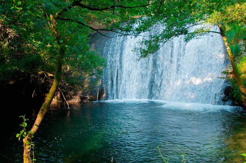 Preciosa cascada de San Xusto entre verdes árboles. 20 lugares que ver en Galicia imprescindibles. Perder el Rumbo