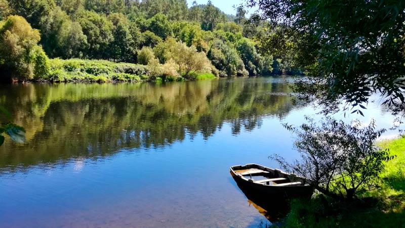 Río en las inmediaciones de Ribadavia. Se ve una barca de madera en la orilla del río y un paraje verde precioso. 20 lugares que ver en Galicia imprescindibles. Perder el Rumbo