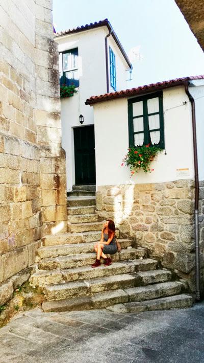 Chica sentada en una escalera de piedra en la entrada de una casa en Ribadavia. 20 lugares que ver en Galicia imprescindibles. Perder el Rumbo