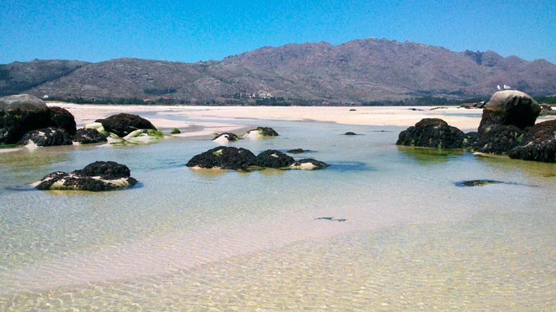 Playa de Carnota y el Monte Pindo al fondo en un día de cielo despejado y azul. 20 lugares que ver en Galicia imprescindibles. Perder el Rumbo