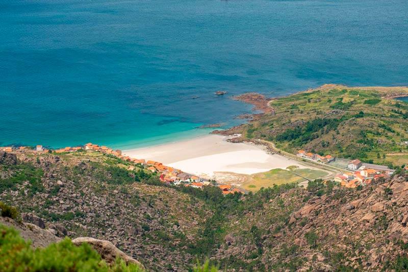 Playa de O Pindo vista desde el monte Pindo. Una preciosa playa con un gran arenal rodeada de verde vegetación. 20 lugares que ver en Galicia imprescindibles. Perder el Rumbo