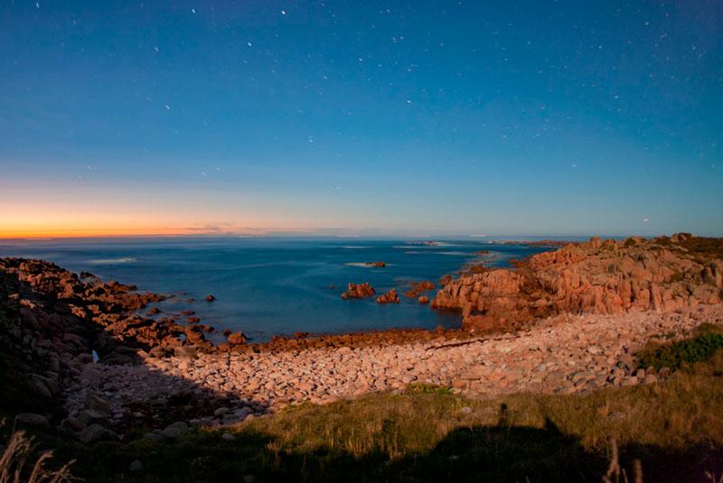 Fotografía nocturna en A Costa da morte. Se ve una playa de piedras y el cielo estrellado. 20 lugares que ver en Galicia imprescindibles. Perder el Rumbo