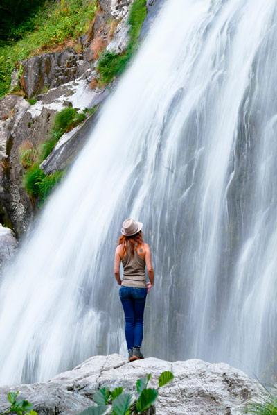 Plano donde se ve una cascada con una chica delante. Es la cascada del Río Belelle. 20 lugares que ver en Galicia imprescindibles. Perder el Rumbo