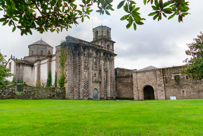 Monasterio de Monfero con una verde prado que lo rodea. 20 lugares que ver en Galicia imprescindibles. Perder el Rumbo