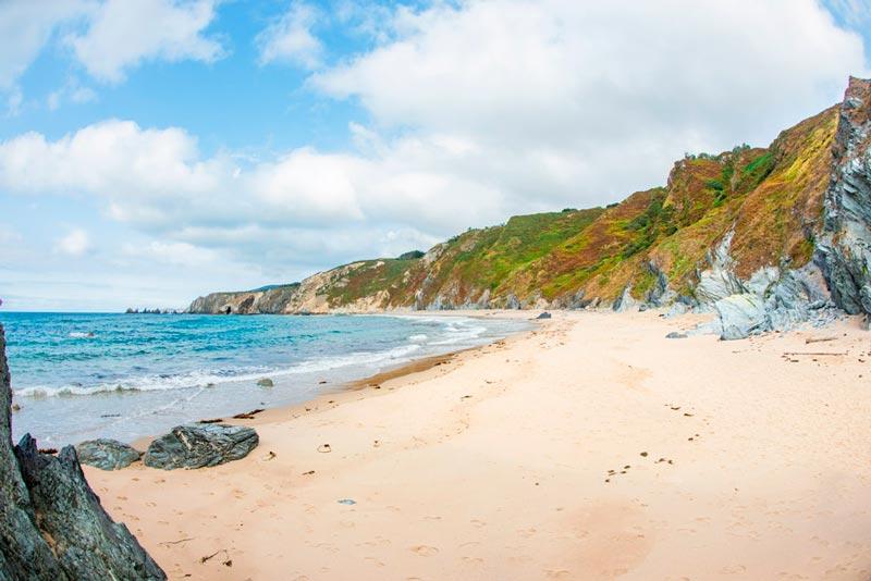 Playa en los acantilados de Loiba con verdes acantilados alrededor. 20 lugares que ver en Galicia imprescindibles. Perder el Rumbo