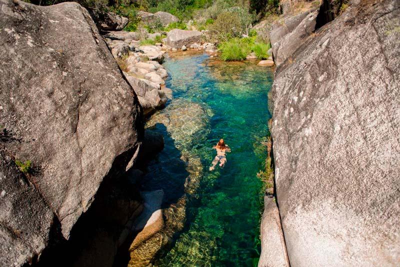 Chica bañándose en las aguas cristalinas de Corga da Fecha en Baixa Limia O Xurés. 20 lugares que ver en Galicia imprescindibles. Perder el Rumbo