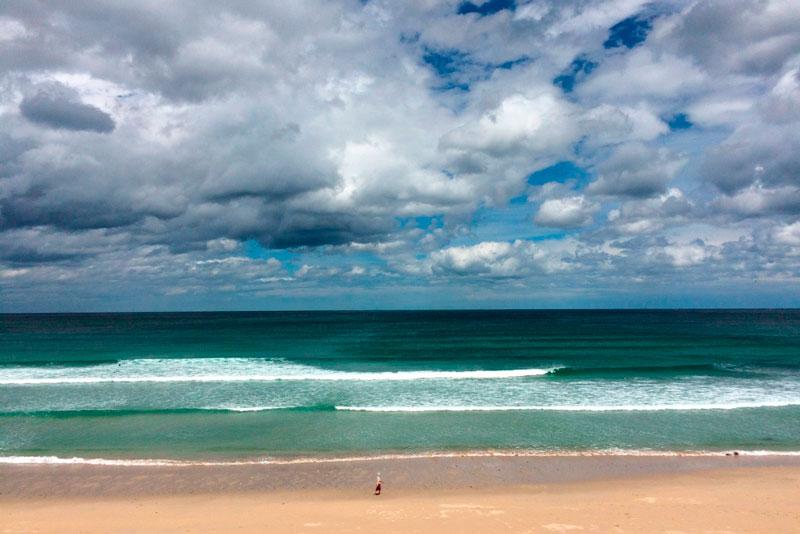 Playa de A Frouxeira. Valdoviño. Se ven las olas, un cielo azul con nubes y una persona diminuta andando por la orilla. 20 lugares que ver en Galicia imprescindibles. Perder el Rumbo