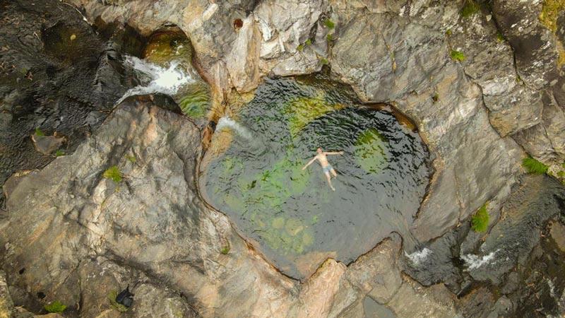 Vista aérea de las pozas del Río Pedras donde se ve a una persona bañándose en el medio de una poza redonda. 20 lugares que ver en Galicia imprescindibles. Perder el Rumbo