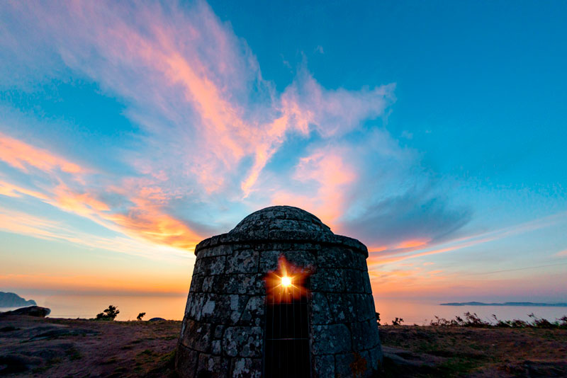 O Facho de Donón en una puesta de sol donde entra por la ventana del facho haciendo un precioso efecto de destello. 20 lugares que ver en Galicia imprescindibles. Perder el Rumbo