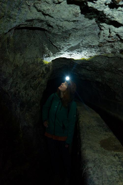 Con una linterna frontal se ilumina el interior del angosto túnel.