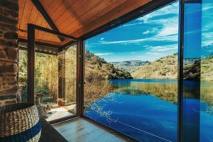 Vistas desde el salón de una casa al lado del río. Se ve la montaña reflejada en el lago en una tarde soleada y azul. Escapada Romántica Galicia. 10 lugares para sorprender a alguien especial . Perder el Rumbo
