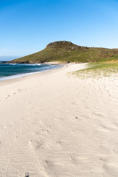 Playa de arena blanca con una montaña al fondo. 15 playas de A Costa da Morte. Belleza salvaje de Galicia. Perder el Rumbo