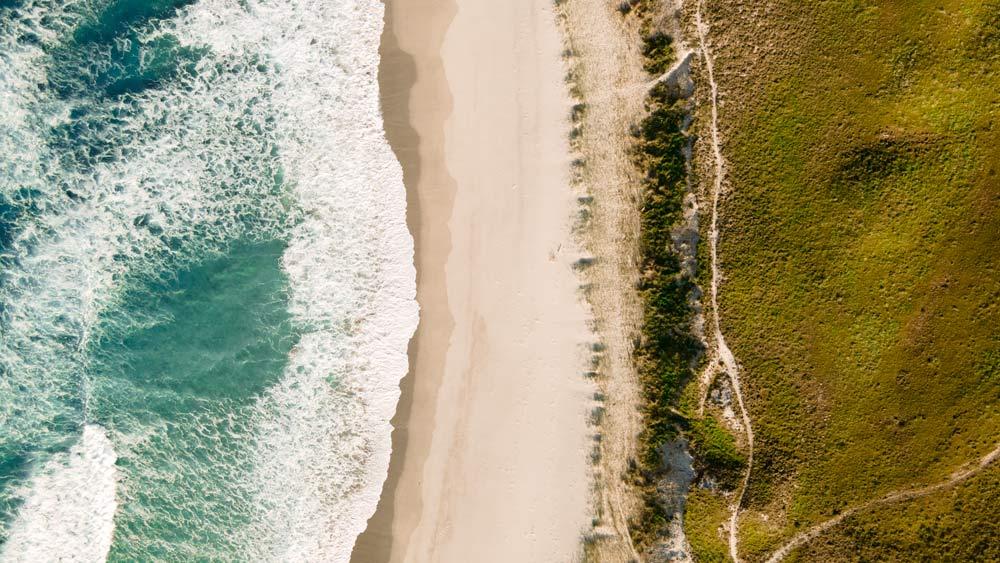 Vista cenital de una playa donde se ve arena, vegetación y agua. 15 playas de A Costa da Morte. Belleza salvaje de Galicia. Perder el Rumbo