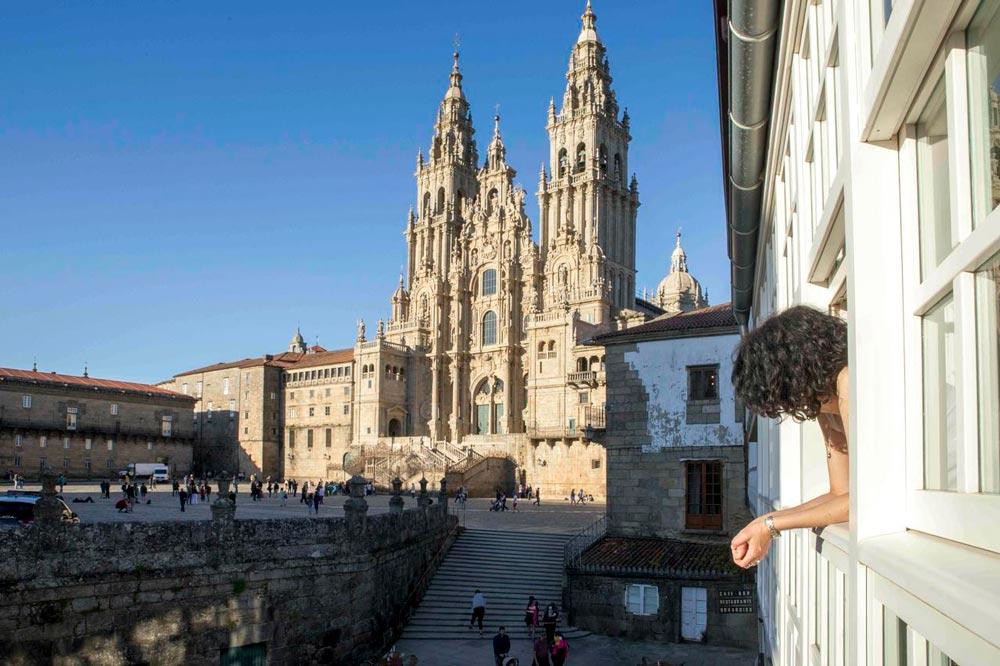 Hotel con vistas a la catedral de Santiago de Compostela. Se ve una chica asomada a la ventana disfrutando de las magníficas vistas. Descubre los 10 mejores hoteles con encanto en Santiago de Compostela. Perder el Rumbo