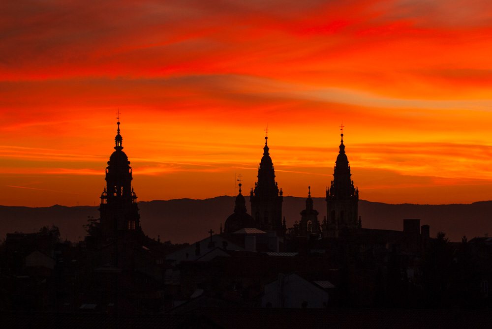Atardecer en Santiago de Compostela. Se ven la torres de la catedrañ y un cielo totalmente anaranjado. Descubre los 10 mejores hoteles con encanto en Santiago de Compostela. Perder el Rumbo