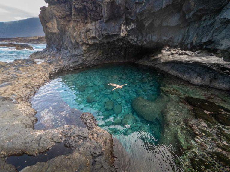 Una persona se baña en una poza de aguas turquesas.