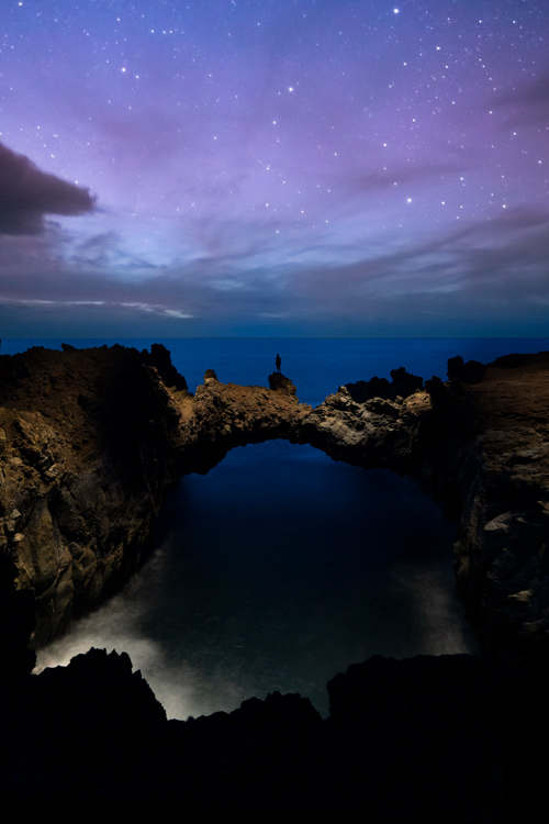 Arco volcánico imprescindible que ver en el Hierro. Foto nocturna donde se ve a una persona muy diminuta sobre él marcando las dimensiones del lugar.