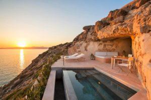 Terraza de la habitación de un hotel con piscina en un gran acantilado. Al fondo la puesta de sol. 20 alojamientos originales en España