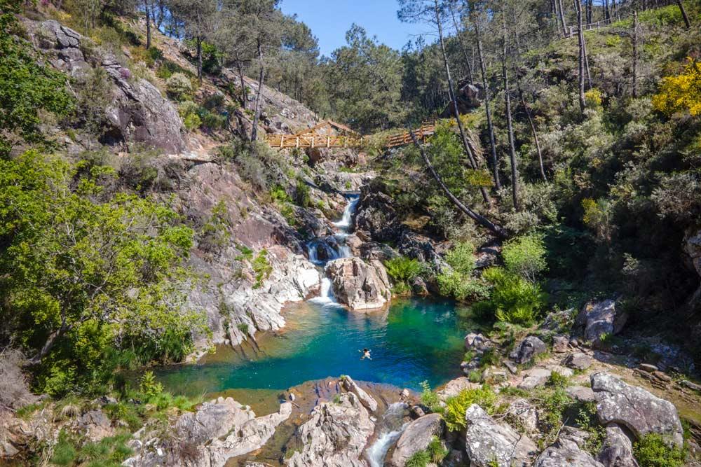 cascada con una gran piscina natural y un puente colgante de madera. 11 espectaculares cascadas en Pontevedra