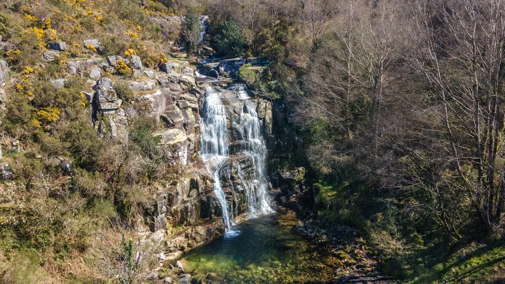 Cascada vista desde el aire con una poza cristalina, rodeado de árboles. 11 espectaculares cascadas en Pontevedra