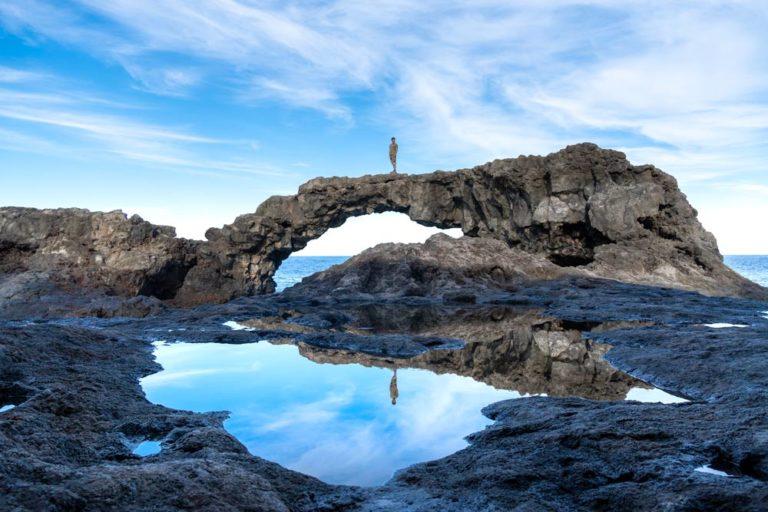 Arco volcánico con una persona en el medio, parece un puente.