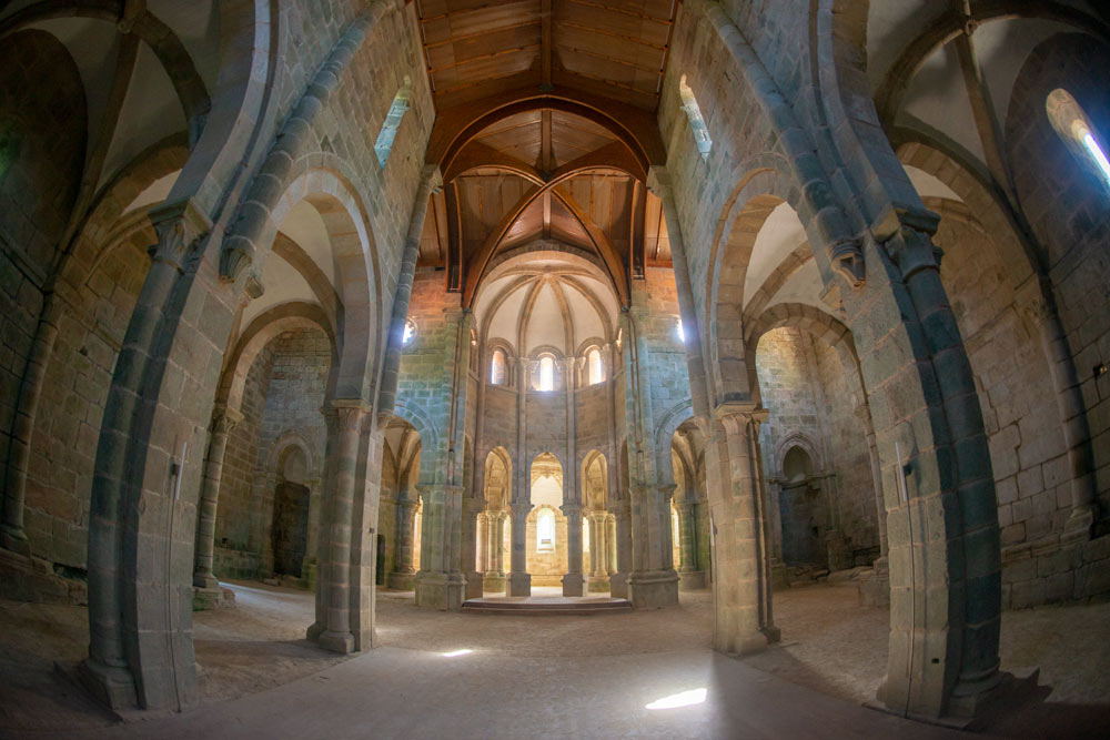Hermosos interior de un monasterio de piedra con bellos capiteles y columnas y una hermosa luz que ilumina el lugar entrando por las pequeñas ventanas. Monasterio de Carboeiro. Visita, ruta y leyenda en Silleda