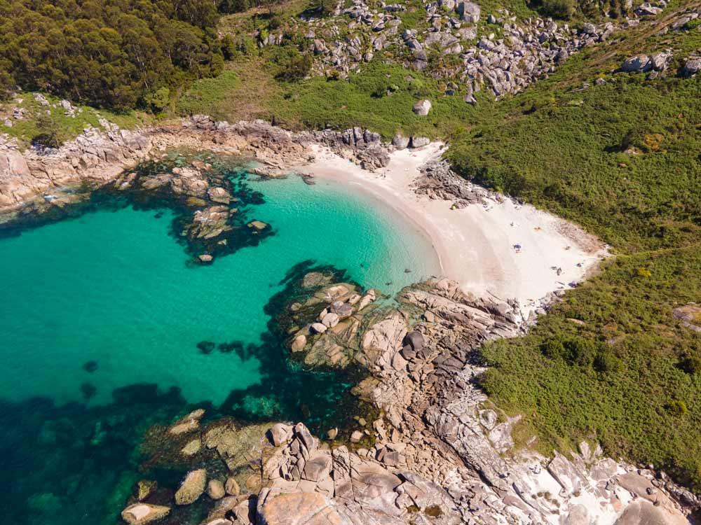 Vista aérea de una cala salvaje rodeada de vegetación. 12 playas de Cangas do Morrazo. El caribe gallego