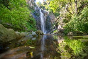 Cascada espectacular con el reflejo en una piscina natural. A Fervenza do Toxa. Una ruta inolvidable