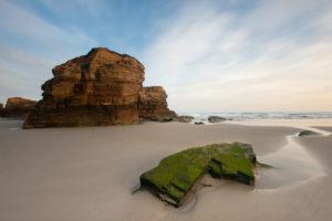 Arenal con formaciones rocosas impresionantes. 15 maravillosas playas de Lugo
