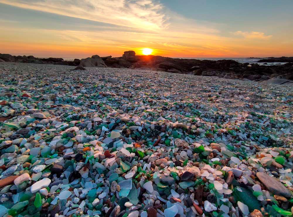 Arenal de trozos pulidos de cristales en una puesta de sol. Playa de los Cristales. Laxe y Cabo Silleiro