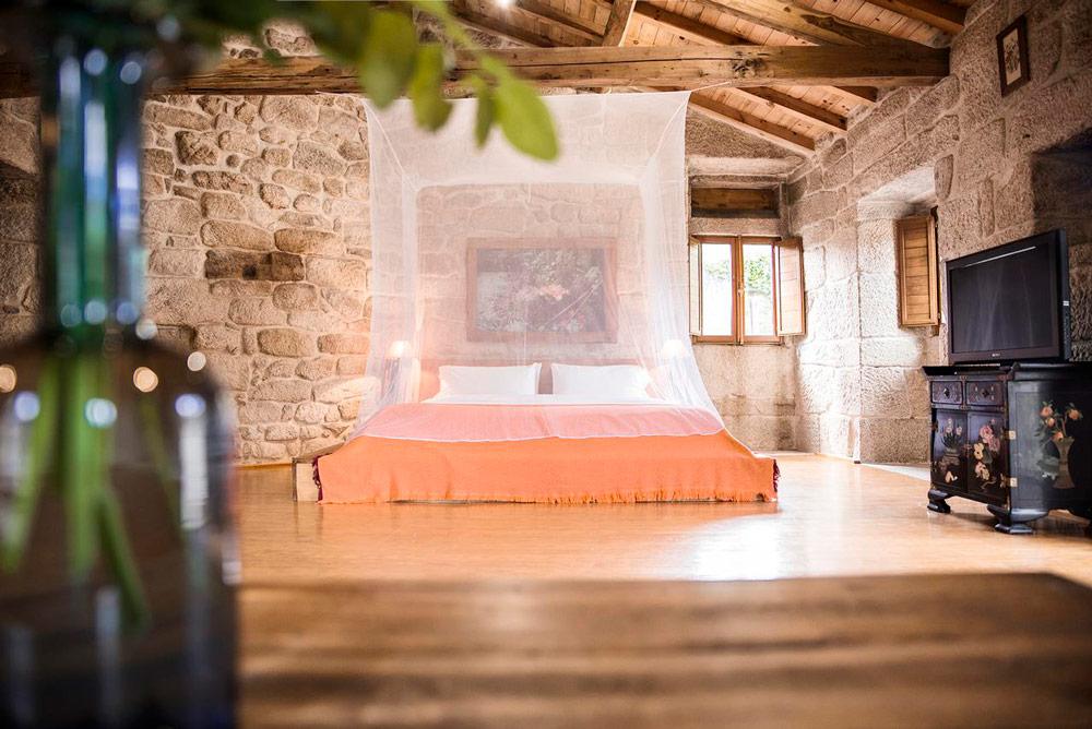 Preciosa habitación con una enorme cama con mosquitera. Paredes de piedra y techos de madera. 10 casas rurales en Ourense con mucho encanto. Perder el RumboCasas rurales en Ourense con encanto. Perder el Rumbo