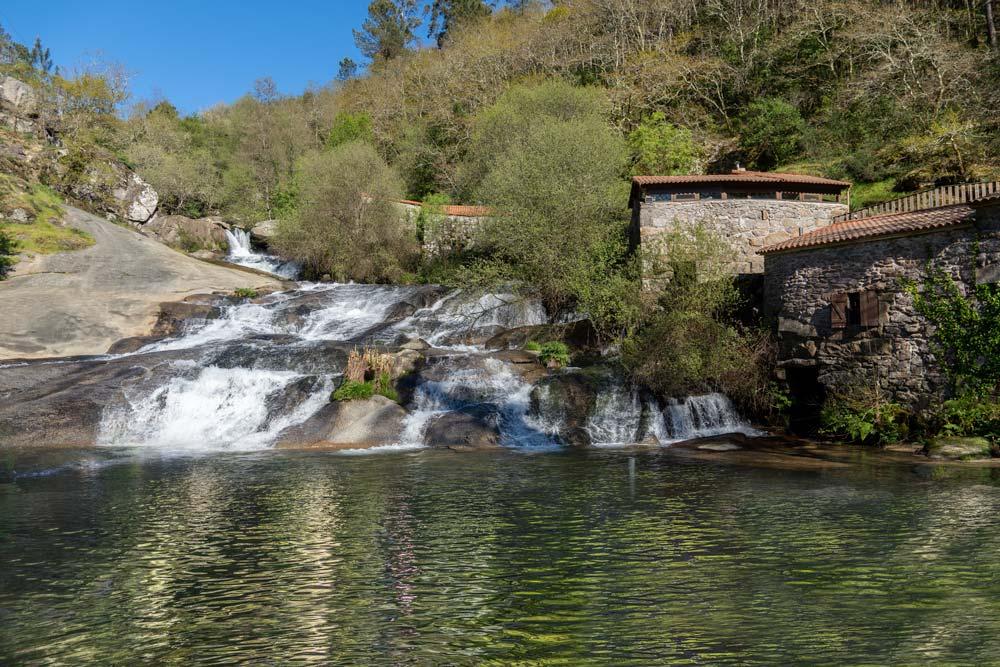 Gran caída de agua al lado de unos molinos de piedra, rodeada de árboles. Río Barosa. Parque de la Naturaleza