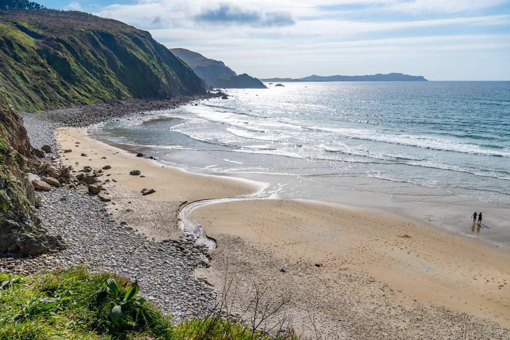 Playa de arena y cantos rodados con verdes acantilados que la rodean. 5 maravillosas Playas de Valdoviño. Perder el Rumbo