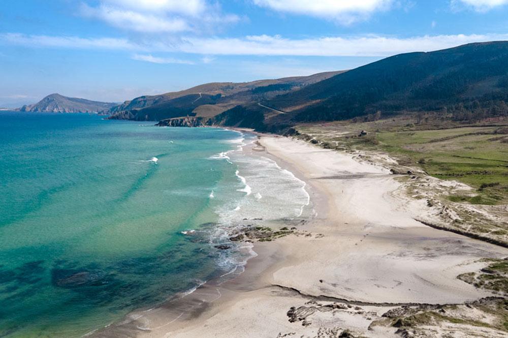 Enorme playa de arena blanca y aguas turquesas. rodeada de dunas y vegetación. 8 Playas de Ferrol que no te debes perder. Perder el Rumbo