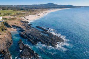 Vista aérea de una gran playa con entrantes rocosos y arena blanca y fina en un día soleado. 10 bonitas playas de Porto do Son en Noia