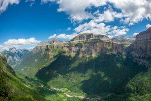 Montañas con verdesvalles y cumbres rojizas. lugares qué ver en Huesca provincia. Descubre sus increíbles paisajes.